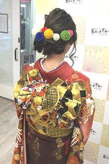 トップからの編み込みで落ち着いた雰囲気を出しながらバックスタイルに和の雰囲気の丸いお花の髪飾りをたくさんつけたキュートなヘアスタイル♪古典的な振袖にもピッタリです!