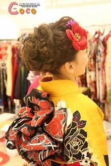 編み込みのアップスタイルに椿の髪飾りがレトロキュート!大胆な明るいお色の髪飾りを顔周りにつけて、お顔を明るく、もっとキュートに♪