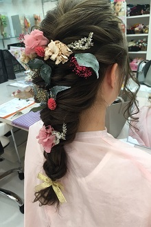 ラプンツェル風のダウンスタイルのゆるい編み込みは去年から根強い人気のスタイル。お花の髪飾りでもっと可愛らしく♪